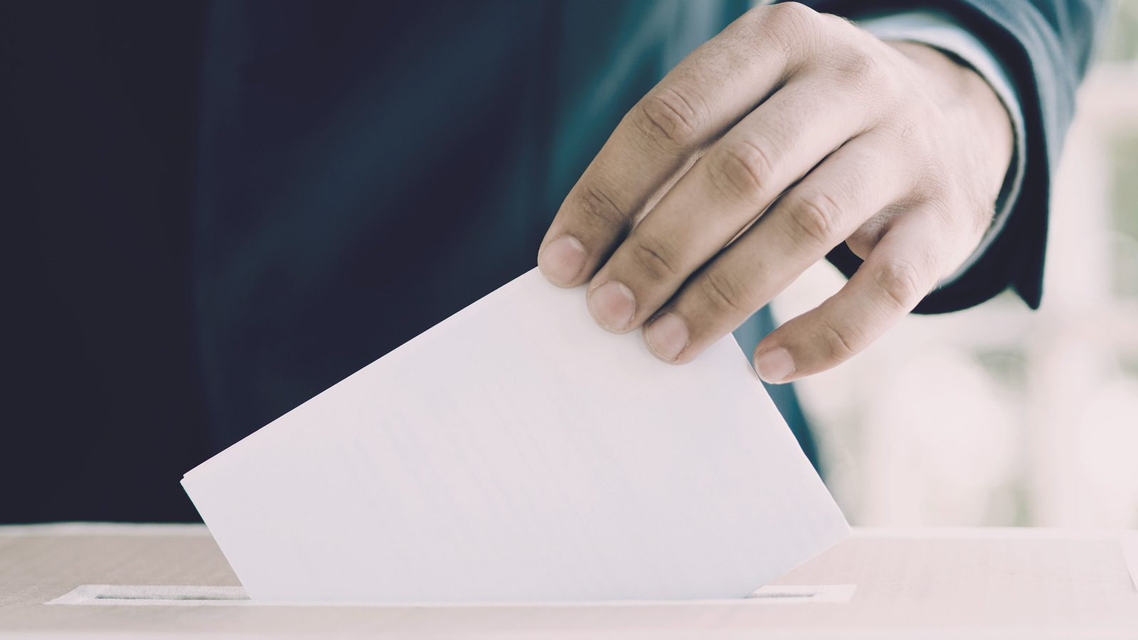 A hand posting a voting slip into a ballot box